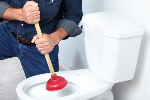 сантехник устраняет засор унитаза